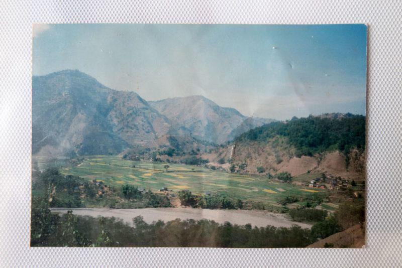 Une photographie du village natal de T. au Népal, dans son album de famille, Nottingham, Angleterre, 12 mars 2017.
